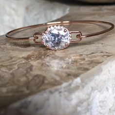 Sterling Silver Rose Gold Plated CZ Oval Bangle Sterling Silver Rose Gold Plated CZ Stone Oval Bangle. This bangle is lightweight and beautiful. The stone is a 10mm CZ surrounded by smaller CZ's in a halo setting. It's a great addition to any wardrobe. Stamped .925 Jewelry Bracelets