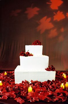 white wedding cake with red floral decoration photo by Yvette Roman Photography