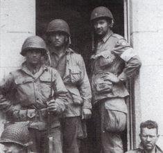 Devant l'hospice de Sainte-Mère-Eglise, quelques jours après le débarquement des hommes de la 4th Infantry Division posent avec des parachutistes du 505th PIR de la 82nd Airborne. Le para avec les mains sur les hanches est le Père James Wood aumonier de la division.