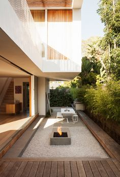 The outdoor living room serves as both a counterpoint and extension of the interior, with amenities that include a Gandia Blasco dining table and bench, a Lynx grill, and a custom concrete fire pit designed by Kathleen Ferguson; it sits atop a bed of crushed white rock. A built-in bench runs along the length of the courtyard.