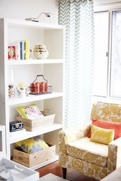 this is such a wonderful corner.  love all the details...the chevron curtain, the patterned chair, the love pillow, the collections on the shelves...perfect