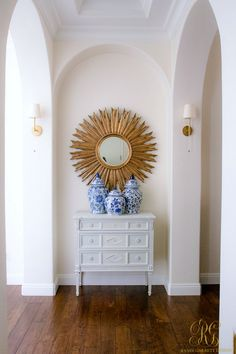 Entry + Hallway with white buffet table, gold sunburst mirror and blue ginger jars - Randi Garrett Design