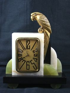 I love the clock face...An Art Deco garniture clock with marble and green onyx surround and a bronze parrot perched to the top corner. CA. 1930.