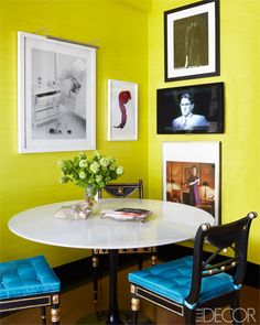 Regency chairs with silk cushions surround a Saarinen table .