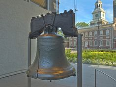 The Liberty Bell sits in the foreground, with Independence Hall visible in the distance.