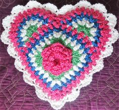 """17"""" Crochet Granny Pink Rose Heart Pillow. Made with colorful, soft bulky yarn and 14"""" heart-shaped pillow form. Solid color back (same color as Rose on front). 17"""" x 17"""". Handmade to order for $25, plus $7 domestic shipping ($23 shipping worldwide). If you would like a different Rose color, please message me. I will be happy to customize your order. Copyrighted Pattern coming soon. The perfect gift to say """"I Love You."""" For Valentine's Day, Mothers' Day, a birthday, or to make any day…"""