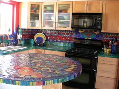 In this true artisan kitchen, Vicky Morrow has created by hand unique and colorful tiling that turns this pleasant kitchen space into an unparalleled work of hue and movement.