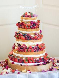 Naked wedding cake decorated with fresh fruit.