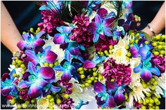 These dyed Blue Dendrobium orchids came out a vibrant turquoise-blue and look amazing with purple orchids, green berries and white mums. Flowers by Petals Floral Design.