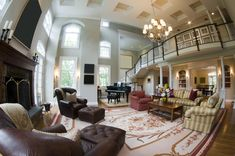 Huge living room with grand piano, large rug, huge fireplace and separate sitting area