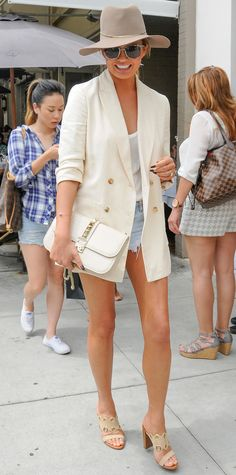 Chrissy Teigen gave her denim cut-offs an elevated spin with a white top, a chic oversize ivory double-breasted blazer, a taupe wool fedora, a studded white purse, and neutral mules.