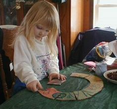Three-year-old Victoria works on a homemade puzzle ring adapted from a Montessori idea