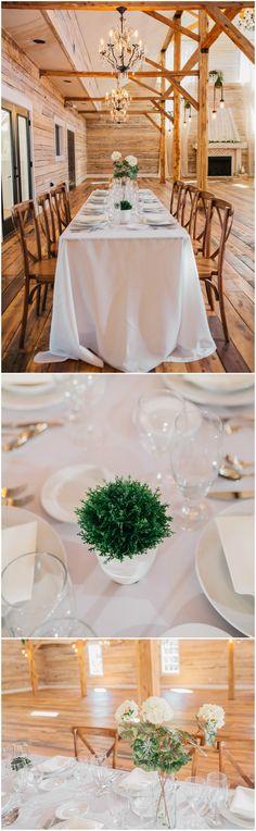 Natural barn wedding reception, chandeliers, white tablecloths, simple centerpieces of greenery, cream florals, wooden cross-back chairs  // Derek Halkett Photography