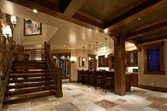 Viewed from the stairs, this home bar is sparsely decorated but still elegant, featuring beautiful rich woodwork and a massive wine cellar visible just beyond the bar. Opulent, love flooring