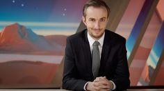 """""""NEO MAGAZIN ROYALE mit Jan Böhmermann"""": Jan Böhmermann sitzt mit gefalteten Händen am Schreibtisch und schaut grinsend in die Kamera. (Ben Knabe)"""