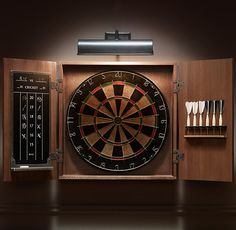 "Restoration Hardware: Tournament Dartboard Set / ""A pub staple on both sides of the pond, darts demands concentration, coordination and no small amount of bravado. Our handsome set encases a self-healing sisal fiberboard, feather-fletched darts and a chalkboard for keeping score, all within an iron-latched oak cabinet."""