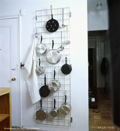 Saucepans on large wall-mounted metal storage rack | 	© living4media | EWAStock…