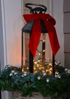 farol negro con luces navideñas y lazo rojo