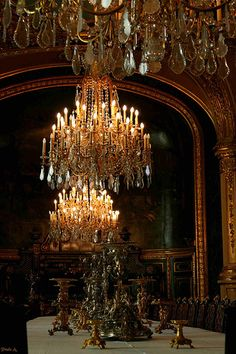 darkly lit room with chandeliers in English manor style.