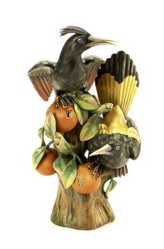 Aves exóticas com frutos num ramo, grupo escultórico em biscuit moldado e relevado da Vista Alegre. Decoração polícroma realista pintada à mão. Marcado V.A. Portugal a dourado, a verde e incisa. Alt. aprox.: 43,2 cm.