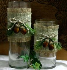 Glass dollar store vases wrapped in burlap. Embellish with greenery,twine and acorns.