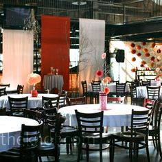 Modern meets shabby chic was the goal for the event space in Denver's Mile High Station. Potted Aspen trees in galvanized buckets adorned with paper flowers and hanging crystals, silk fabric panels, and strategic lighting transformed the industrial space.