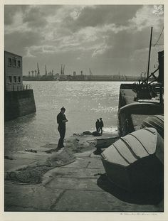 "John Neary,Liverpool`s last full time fisherman pictured mending his nets on the""cockle hole"". Photo by E Chambre Hardman"