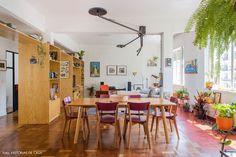 Sala de jantar e estar integradas com muitas plantas, móveis coloridos e armário de madeira como divisória