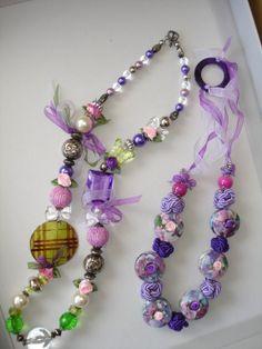 collane di bigiotteria ...perle, microrose in raso, nodi cinesi di passamaneria fatti a mano, bottoni dipinti a mano, cerchio in madreperla viola come chiusura, cromie di voile.. elementi in resina particolari