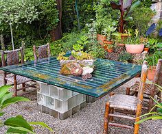 There are many creative ways to make an outdoor table using durable materials capable of withstanding the elements. Here, thick glass-block pillars hold up a tabletop made from a sheet of industrial glass. The transparent quality of the table keeps the focus on the beautiful plantings surrounding it.
