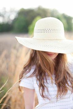 une femme dans le champs de blé avec un chapeau de paille blanc