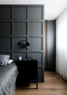 dark grey walls, grey bedding, black bedside table