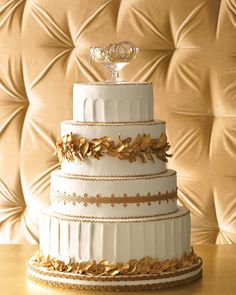 """Grecian Gold headdresses of flowers and foliage made their mark during the Hellenistic period, and here, they make for a fitting cake motif. Made of gum-paste flowers painted with gold luster dust, the wreaths, along with the Corinthian column-inspired tiers, turn this cake into a Greek fantasy. Encircled in real ribbon and topped with a champagne coupe bubbling over with a necklace, of course. """"Trinity Crash"""" necklace, Cartier."""