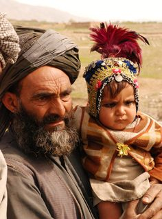 Kuchi nomad holds a child wearing traditional headdress :: Afghanistan