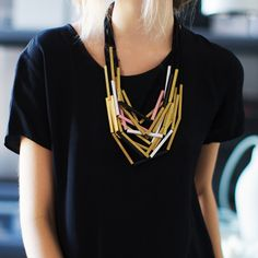 Gold and black necklace and plain black shirt...