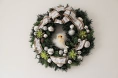 Christmas wreath with silver/gray ribbon.  Using artificial succulents and silver color ornaments.  It measures approx. 18 diameter.