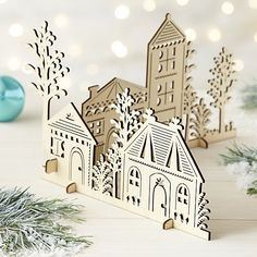 Set up a miniature village of laser-cut wood structures with charming architectural detailing and tree silhouettes. Two sections piece together and stand on removable feet. Create a winter wonderland with coordinating laser-cut trees and animals.