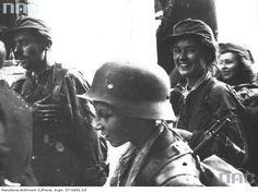 "Soldiers from Group ""Radosław"" after a several hour sewer march from Plac Krasińskich to ul. Warecka in Śródmieście district, early morning on September 2, 1944. The boy wearing a helmet in front is Tadeusz Rajszczak ""Maszynka"", behind him is Wiesława Reiff ""Sława"" - both from ""Miotła"" Battalion."
