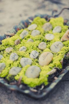 Pebble 'place cards' set in a basket of moss - great rustic/boho wedding idea!