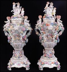PAIR OF DRESDEN PAINTED AND GILT PORCELAIN COVERED URNS. Bearing applied floral and putti decoration 28.5'' x 12''