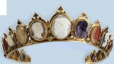 Close up of diadem designed as a line of graduated cameos carved in various hardstones, amethyst, carnelian, and agates set within a red and blue enameled moun