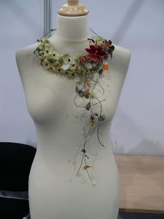 A floral necklace is a unique and contemporary way to wear flowers.  A simple or statement fresh or artificial flower necklace is a great way to accent a strapless or off-shoulder bridal / wedding gown or bridesmaid dress.