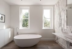 Modern white bathroom in UK with freestanding bathtub and marble slab wall