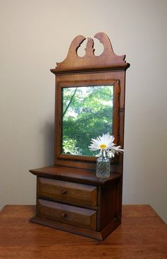 Well-made pine cabinet with mirror to hang on the wall or sit on a counter or table for storage of small items. Use it for spices, apothecary, for shaving supplies or vanity items. It could hold a small selection of sewing notions, if your need for sewing storage is not great. The cabinet is made entirely of solid wood, looks like pine to me, in 3/4, 5/8 and 3/8 lumber. It is stained and varnished in a dark honey color and slightly distressed. The drawers are clean, slide easily and the…