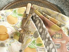 Fresh-picked fruits scatter about a colorful orchard of pretty paisleys and blossoms in the Clementine Collection by Ana Davis. Orange, green, citron and sky blue hues adorn pots, pans and silverware for a unique charm from farm to table. This delightful collection is ideal for culinary accessories such as dish towels, aprons, pot holders and more.