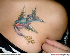 Girl with a cross and swallow tattoo