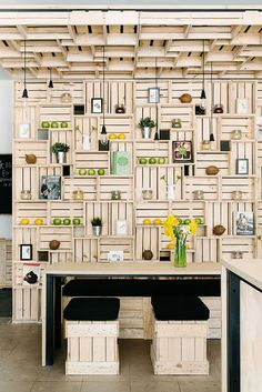 Pressed Juices bar in Melbourne - neutral-toned wall made from wooden crates, also serves as shelves and stools.