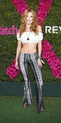 #BELLATHORNE Thorne got groovy at the People StyleWatch x Revolve party in a '70s-inspired look, which consisted of a midriff-baring off-the-shoulder bustier top, flared printed pants. lariat-style necklace, and lace-up sandals. #Coachella