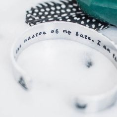 "Make a statement on your arm and set an intention in your heart with this inspirational quote bracelet. The bracelet features a seated buddha figure and a butterfly on the outside and the quote by William Ernest Henley, ""I am the master of my fate. I am the captain of my soul,"" on the inside."