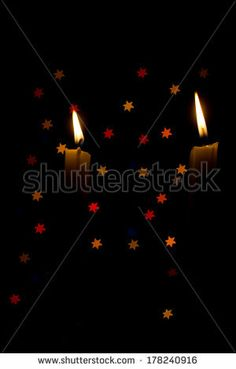 Two candles against a star bokeh black background - stock photo